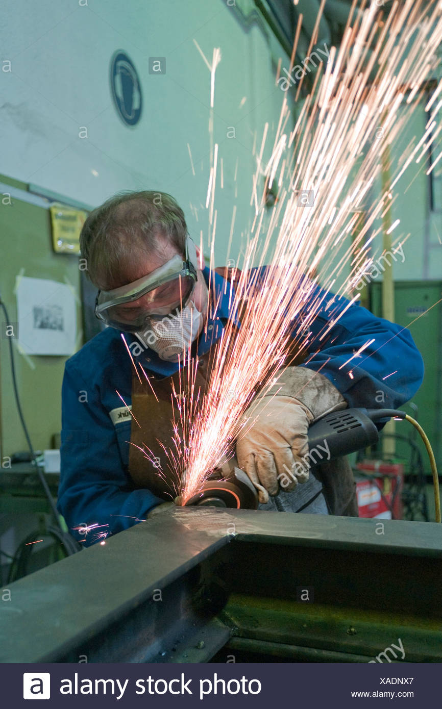 Man with protective goggles and protective clothing working on metal with an angle grinder, Germany - Stock Image