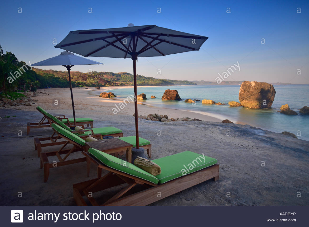 Sun loungers and parasols on beach in morning, West Sumba, Indonesia - Stock Image