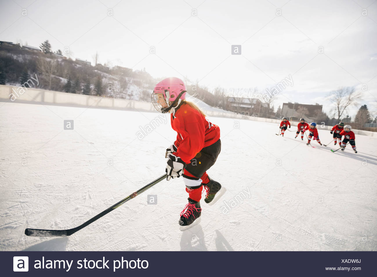 Girl playing ice hockey on rink - Stock Image