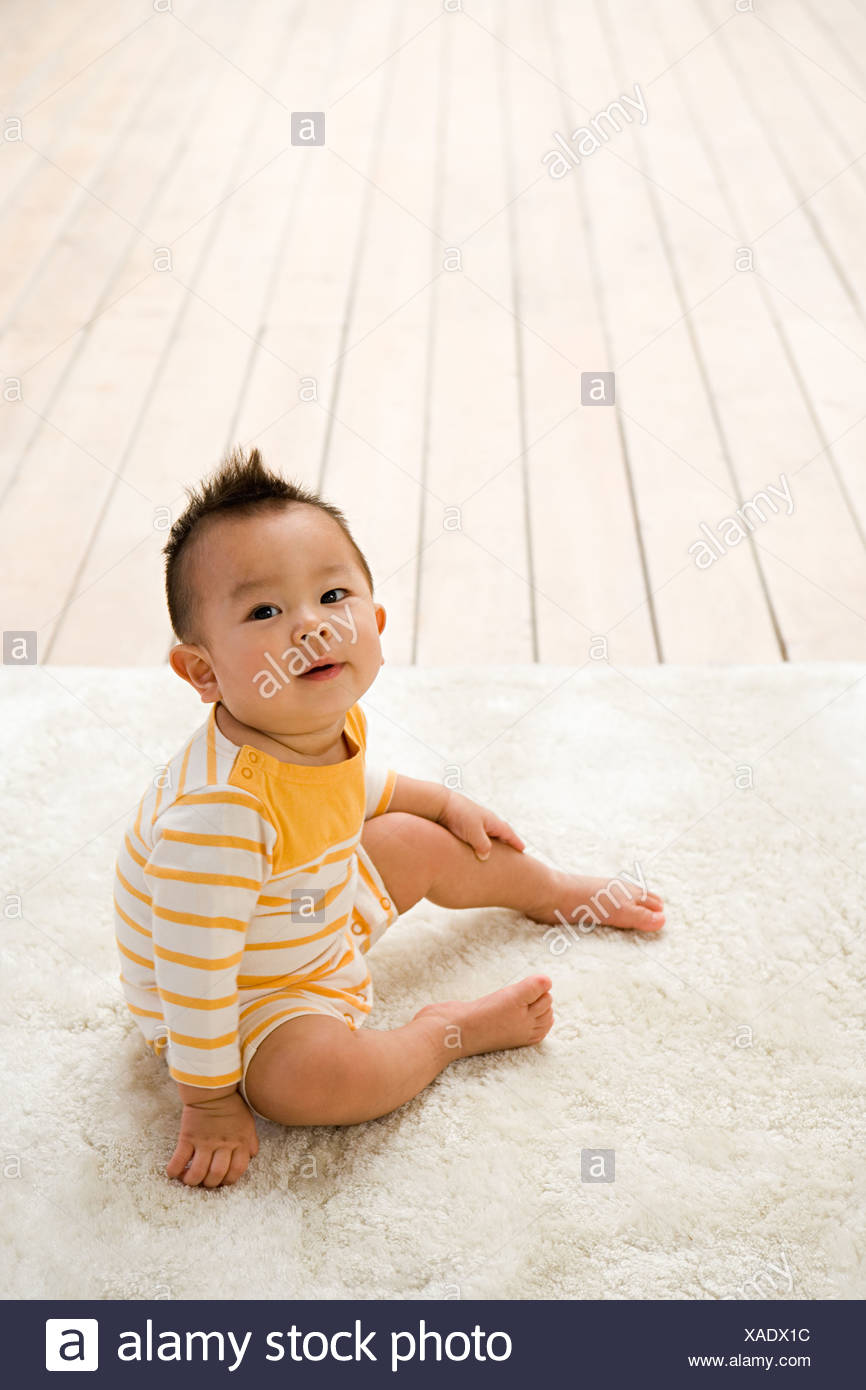 Cute baby sitting on a rug - Stock Image