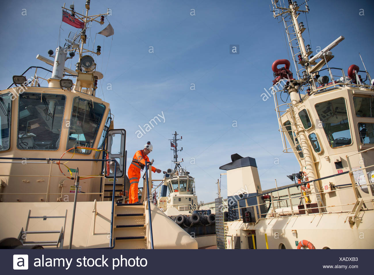 Worker standing on deck of tow boat - Stock Image