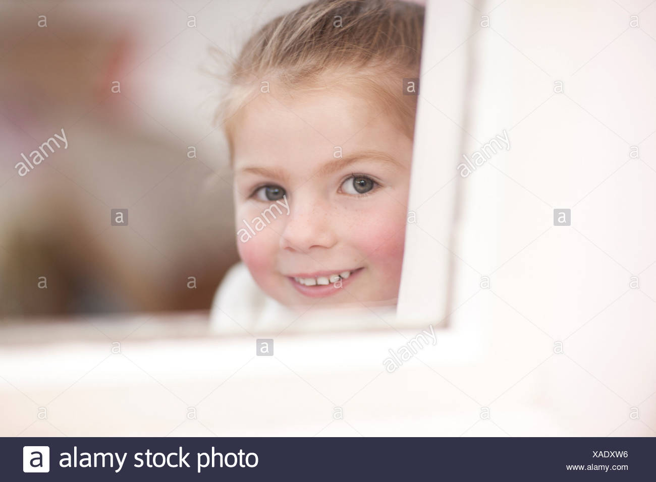 Close up of young girl looking through window at ballet class - Stock Image