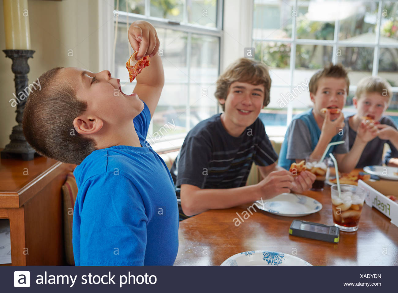 Boy swallowing pizza with mouth open - Stock Image