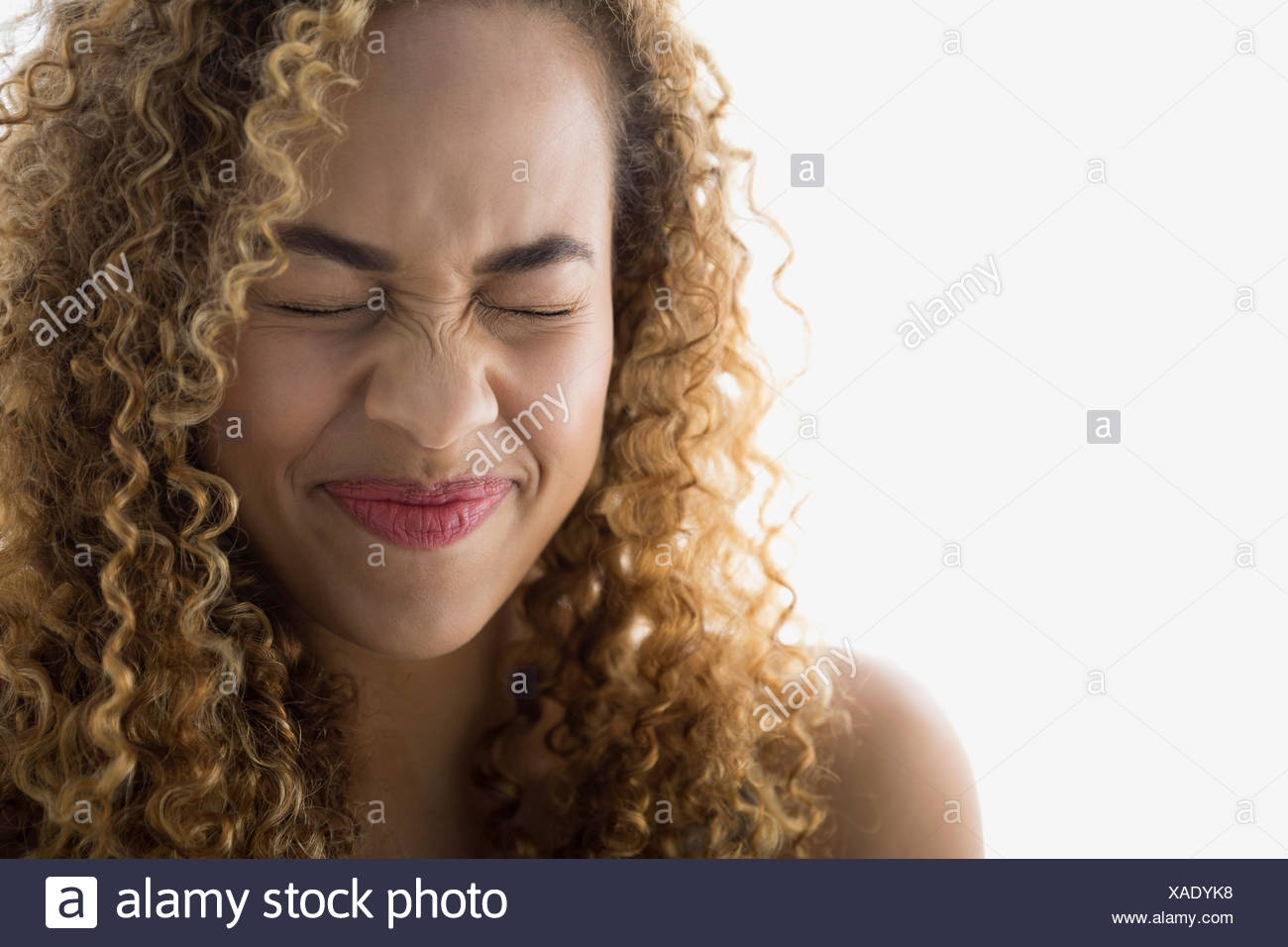 Woman with curly hair making a face - Stock Image