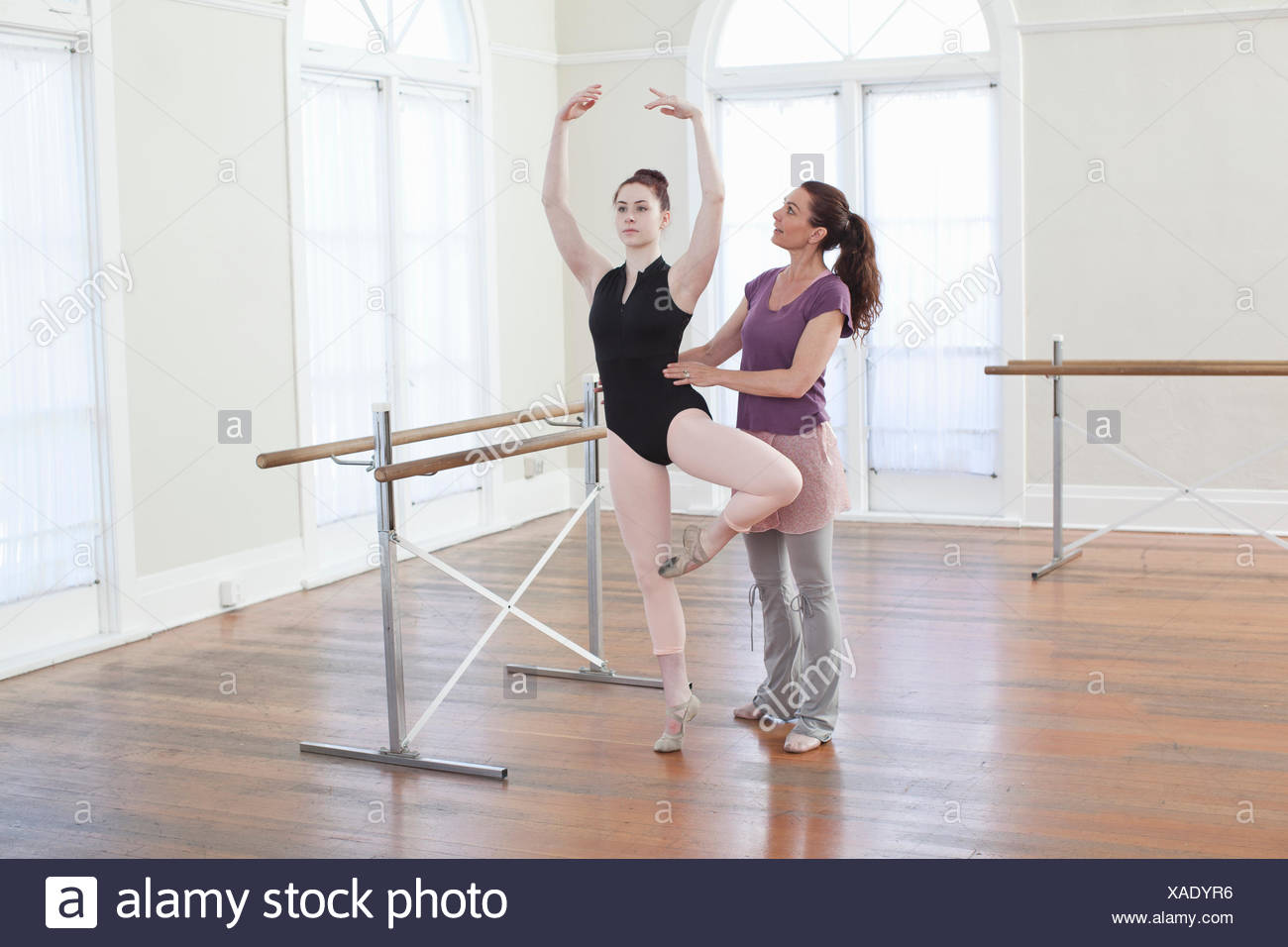 Teacher teaching ballet position to teenage ballerina at ballet school - Stock Image