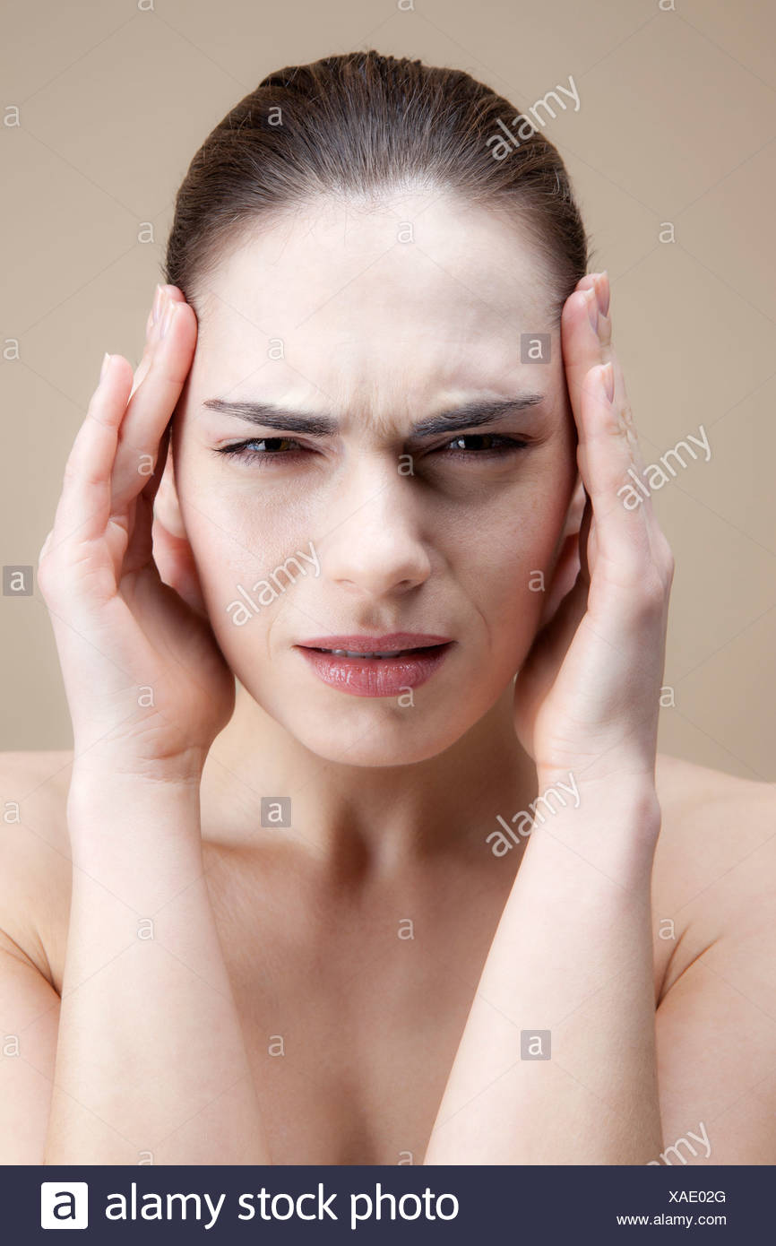 A grimacing young woman with her hands to her temples - Stock Image