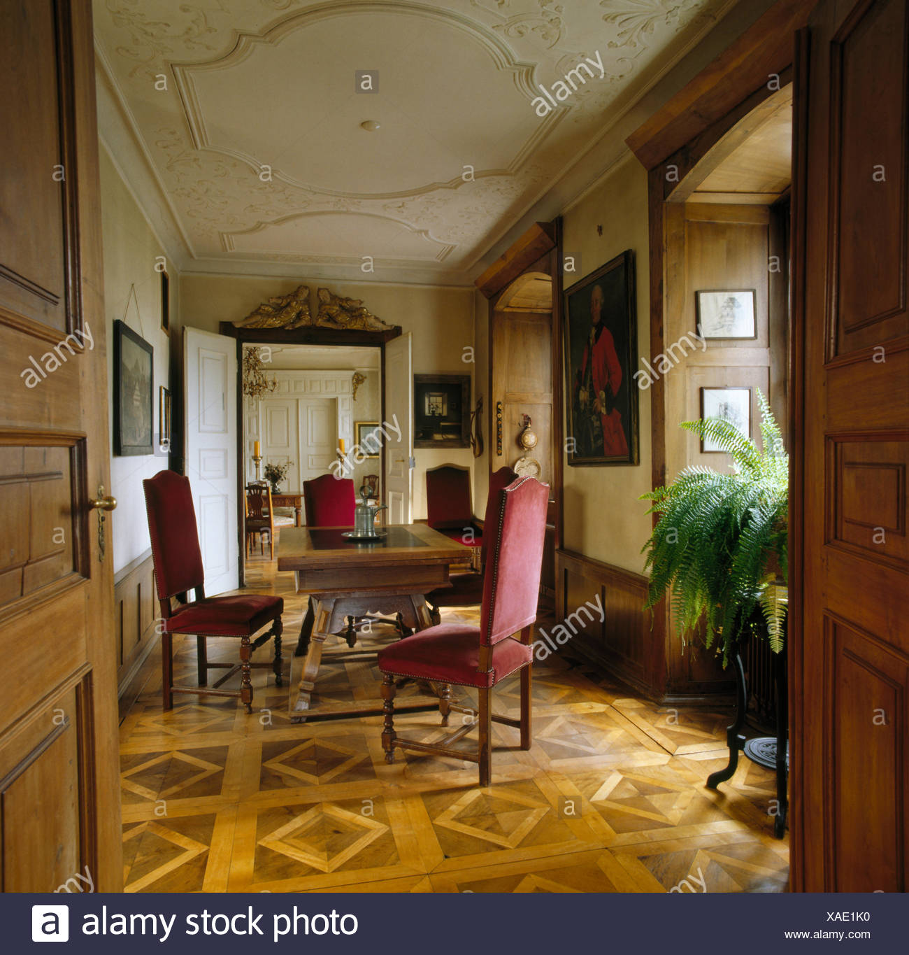 Parquet flooring and antique dining table and chairs in period hall dining room - Stock Image
