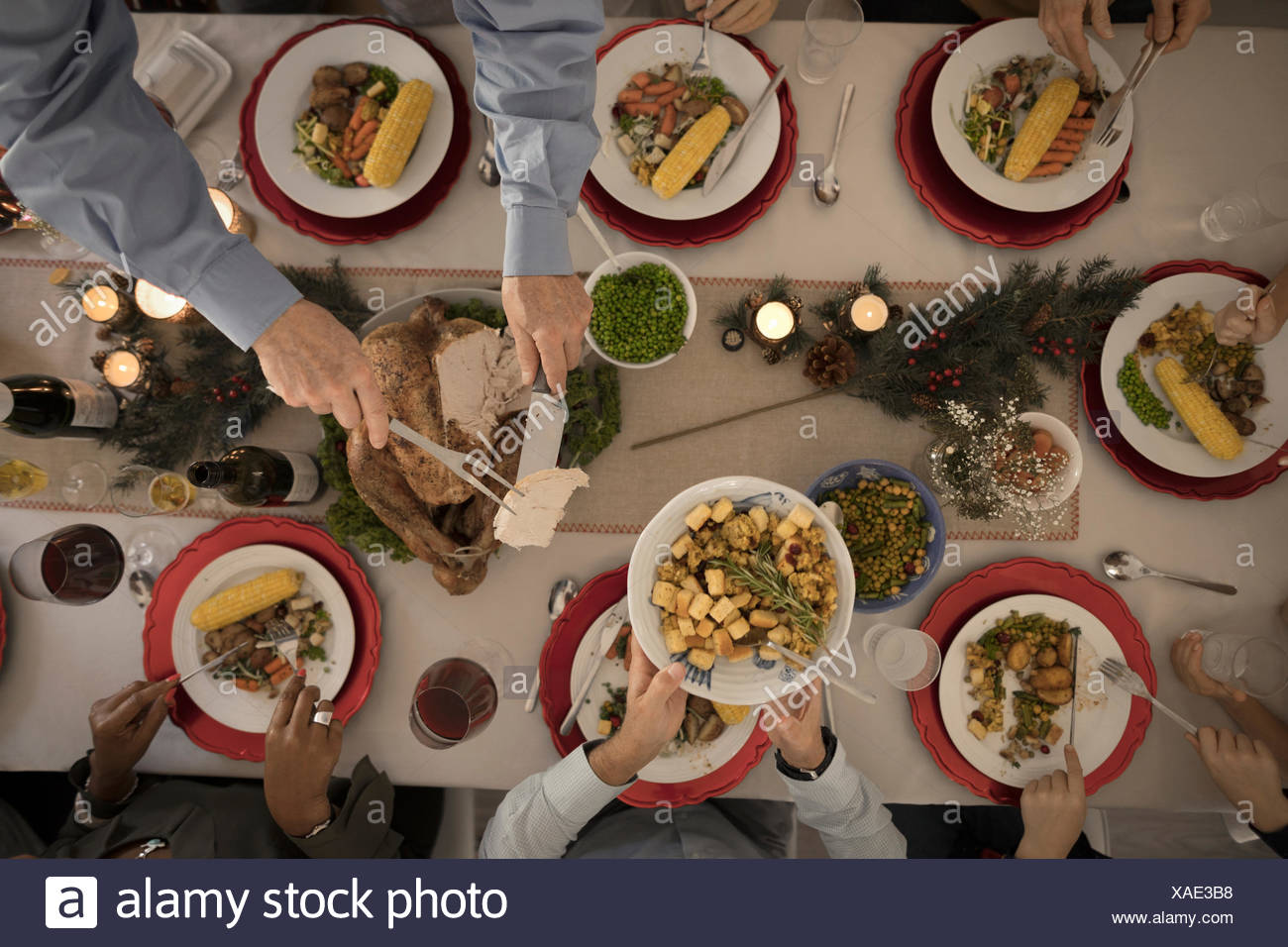 Overhead view family carving and serving turkey at Christmas dinner table - Stock Image