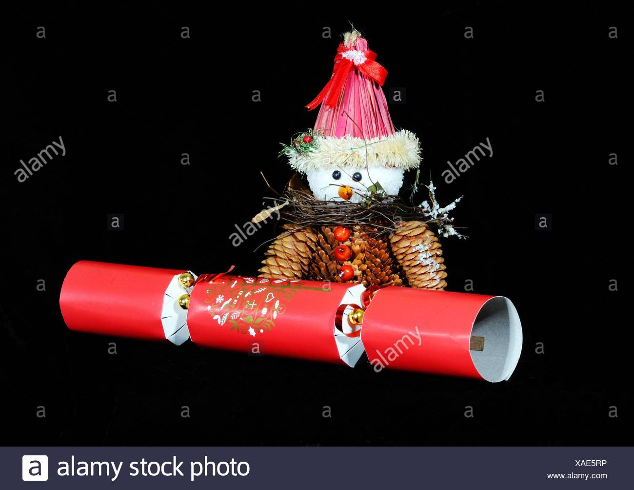 Christmas cracker hats stock photos christmas cracker hats stock snowman made from pinecones with a red christmas cracker set against a black background england solutioingenieria Images