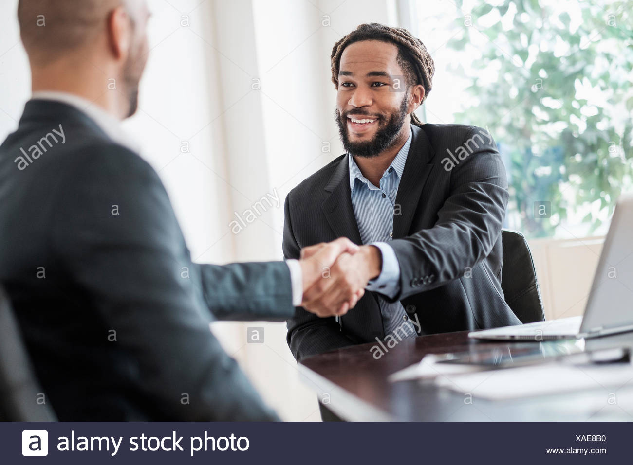 Smiling businessmen shaking hands in office - Stock Image