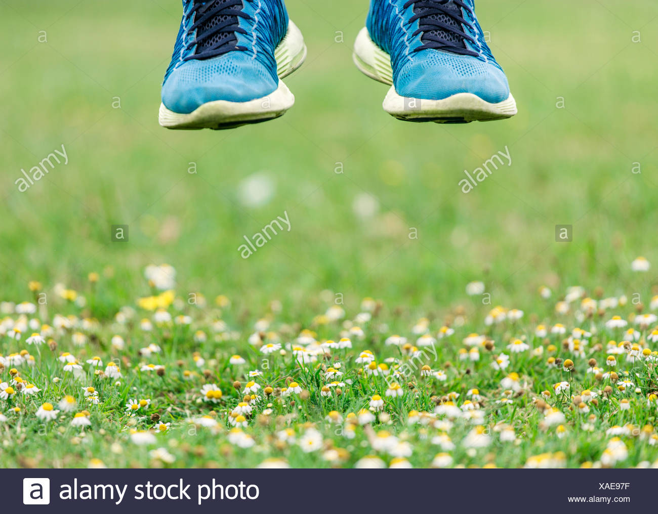 Jumping feet in trainers, mid-air - Stock Image