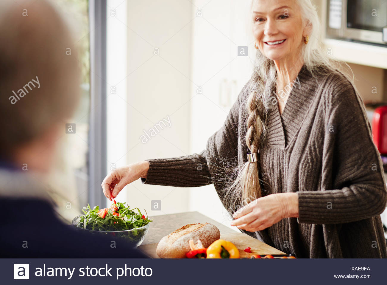 Senior woman preparing food in kitchen - Stock Image