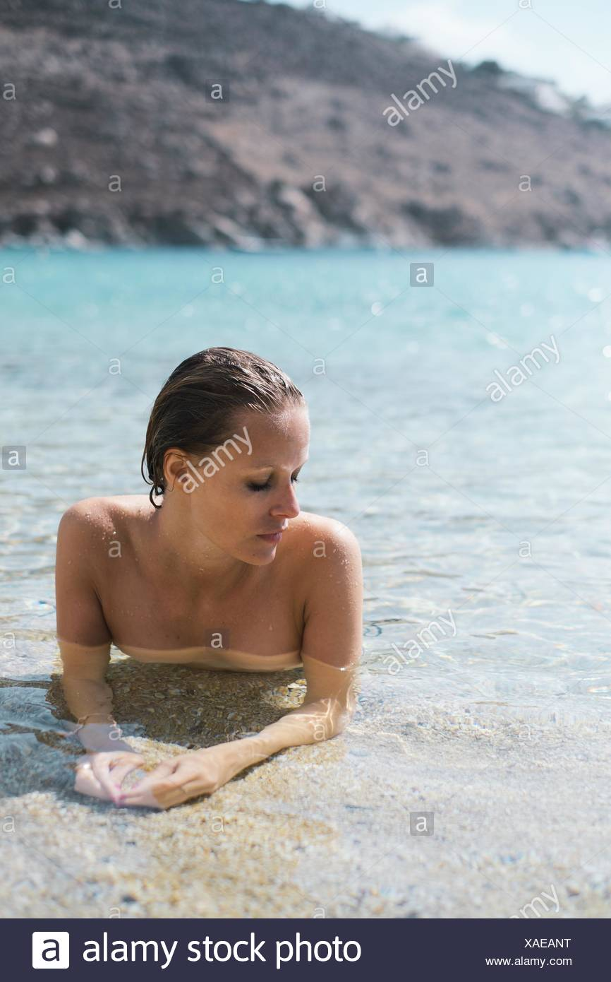 Woman lying in the sea - Stock Image