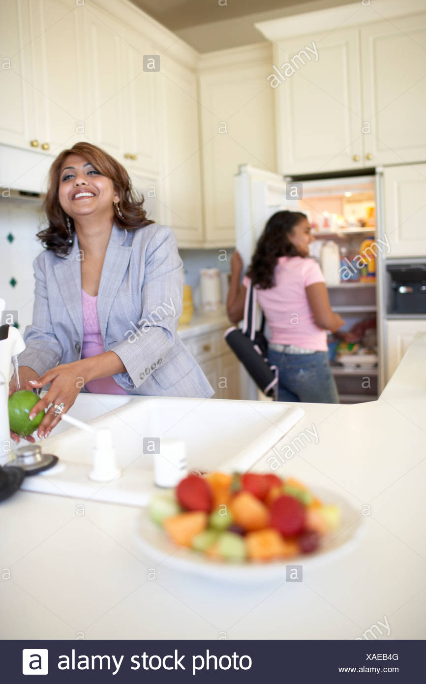 Mother And Daughter Of Indian Ethnicity In Kitchen Stock