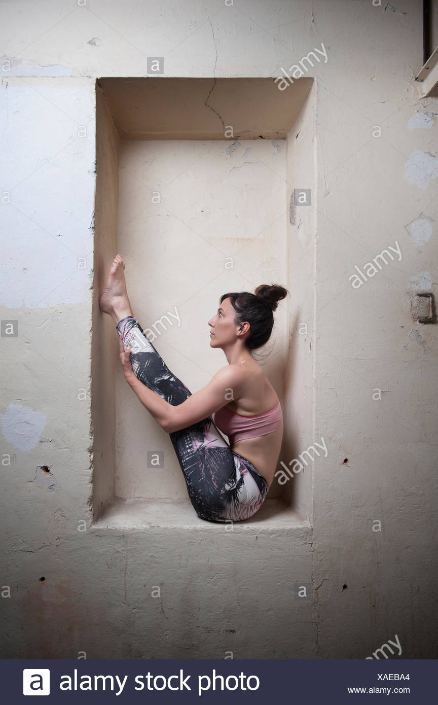 Mid adult woman practicing big toe pose in alcove, Munich, Bavaria, Germany - Stock Image