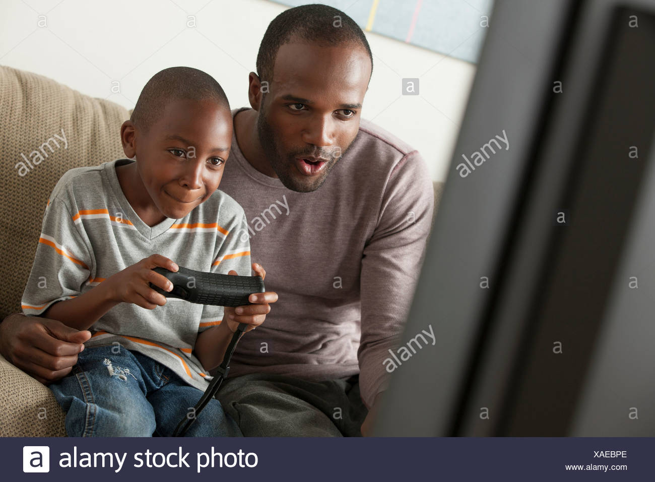 Father and son playing video game - Stock Image