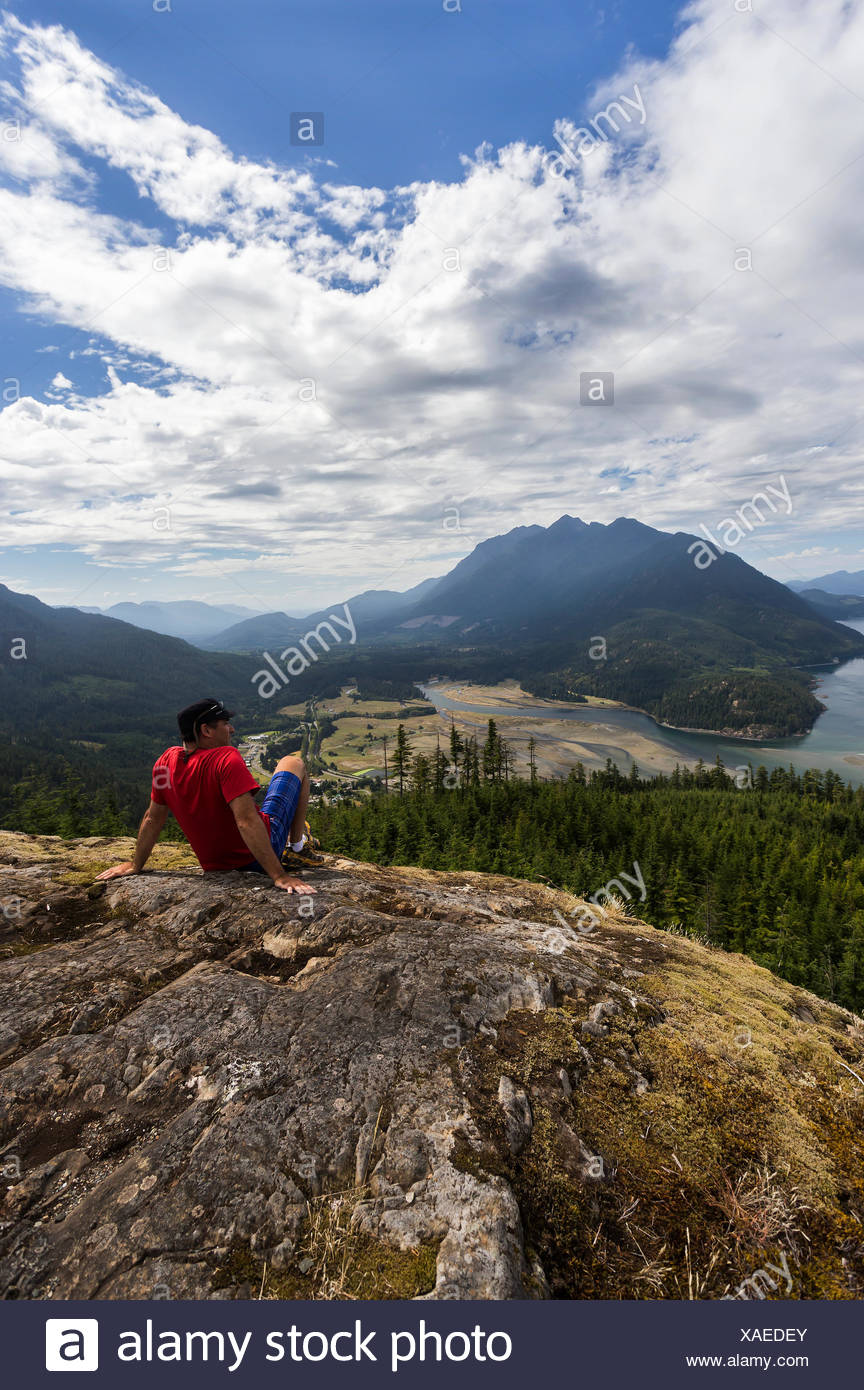 A hiker is rewarded with commanding views of Kelsey Bay and the Salmon River Estuary from a viewpoint high above the valley, Sayward, Vancouver Island - Stock Image