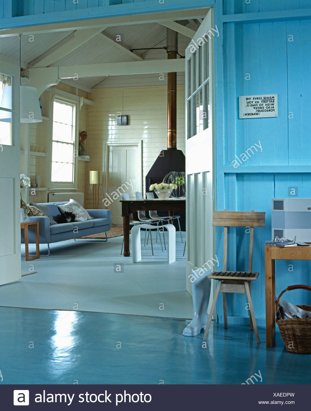 Blue Painted Cottage Hall With Turquoise Vinyl Floor And Panelled Walls View Of Living Dining Room Through Doorway