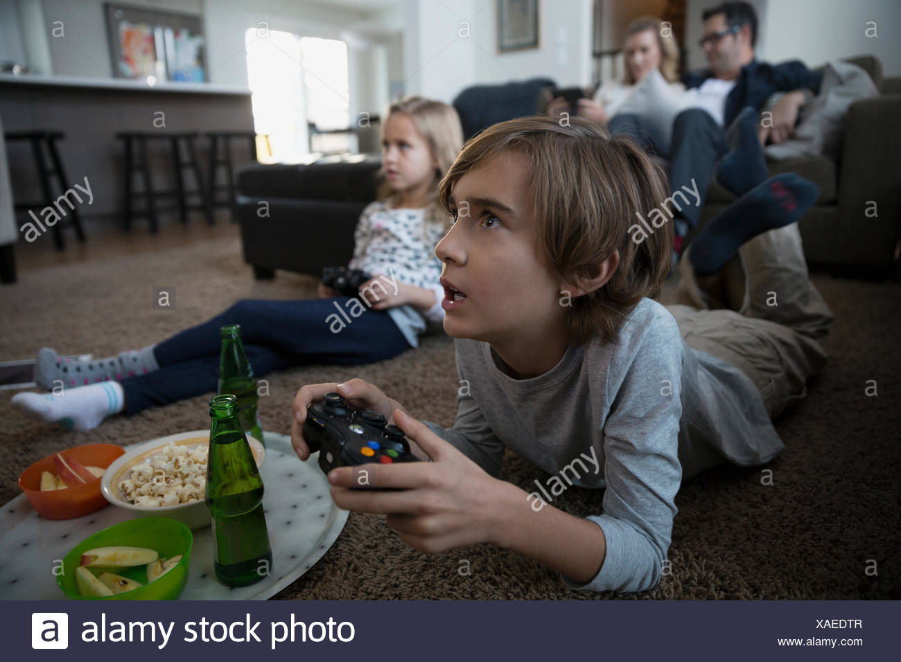Boy with snacks playing video game living room - Stock Image