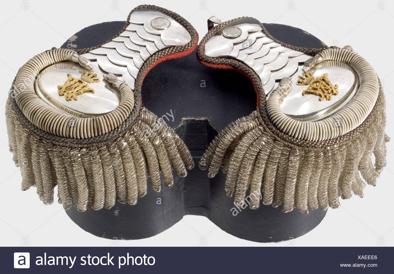 A pair of livery epaulets for a senior court servant, at the Royal Prussian Court. Silver-plated scales, fields with serpentine trim of strong, twisted wire, and overlain with the gilded cipher, 'WR' and the royal crown. Silver bullions, red cloth backing. The star of the Order of the Black Eagle is stamped on the buttons. They come with the box. historic, historical, 19th century, Prussian, Prussia, German, Germany, militaria, military, object, objects, stills, clipping, clippings, cut out, cut-out, cut-outs, utensil, piece of equipment, utensils, item, items, Additional-Rights-Clearences-NA - Stock Image