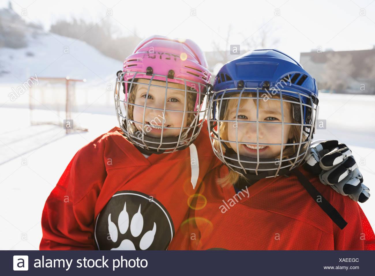 Portrait of smiling girls in ice hockey uniform - Stock Image