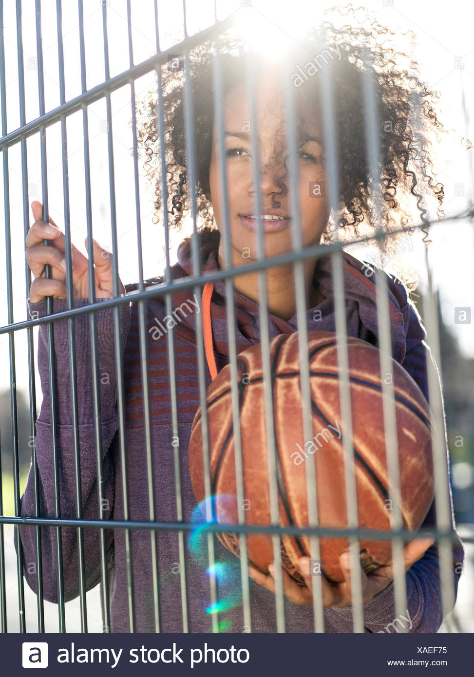 Portrait of young woman with basketball standing behind a fence - Stock Image