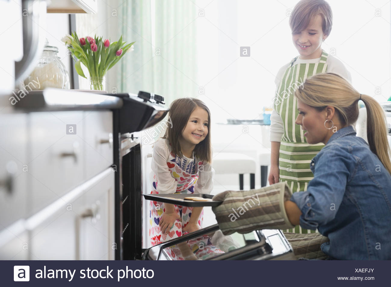 Children and mother baking cookies in kitchen - Stock Image