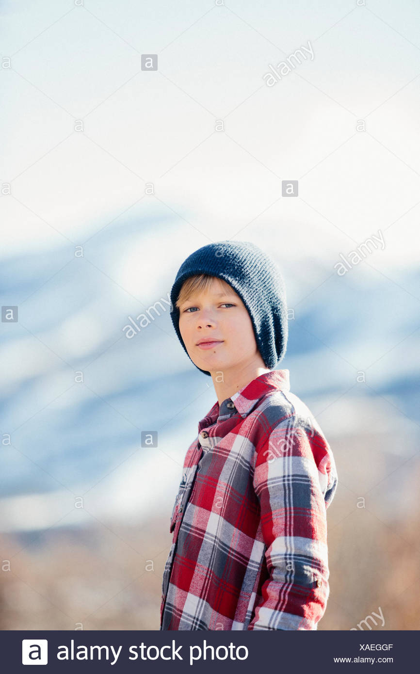 A boy with a woolly hat and checked shirt standing in open countryside in winter. - Stock Image