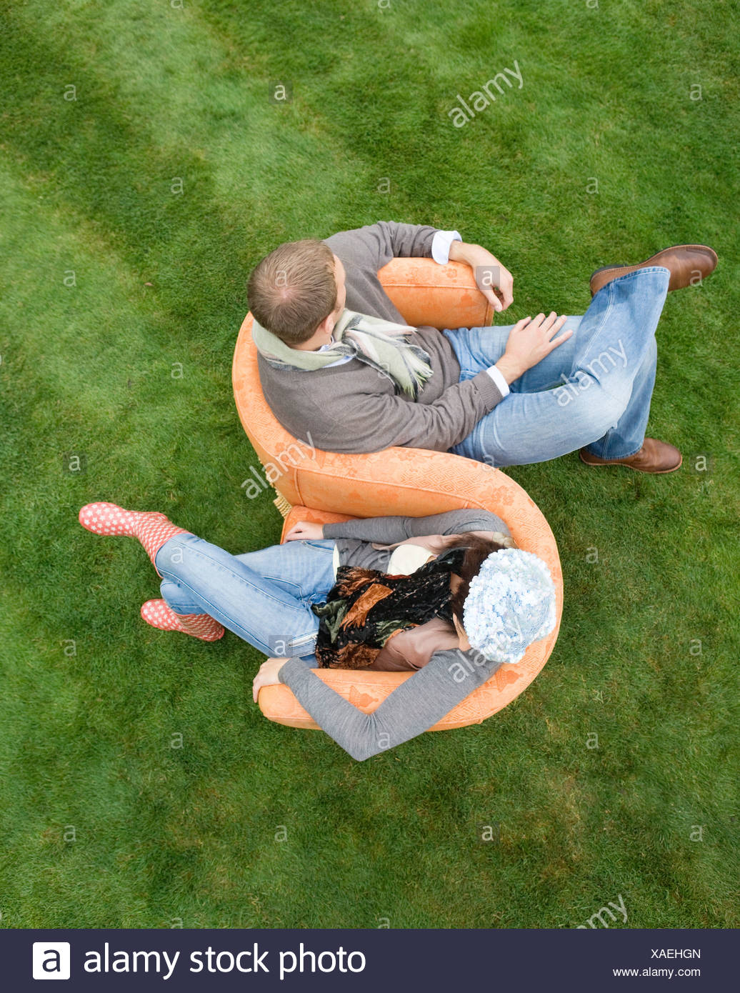 Couple sitting on love-seat outdoors - Stock Image