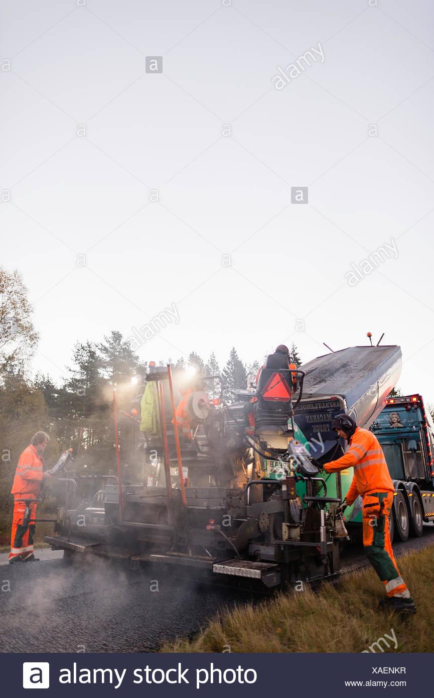 Sweden, Narke, Two manual workers repairing road - Stock Image