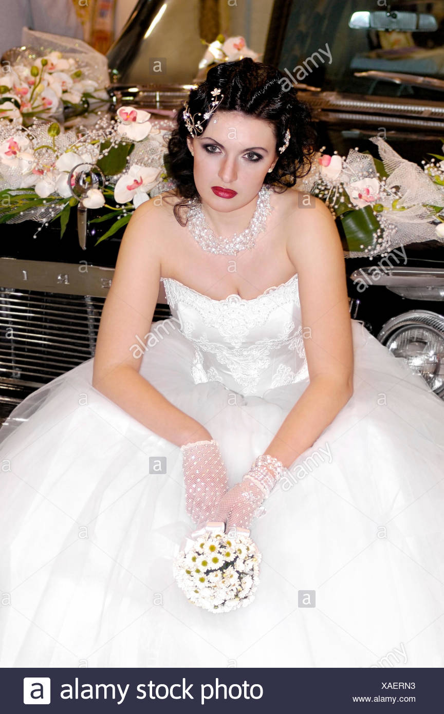 Young Beautiful Woman In White Wedding Dress Sitting Alone On A Car Bumper With Bunch Of Flowers Her Hands