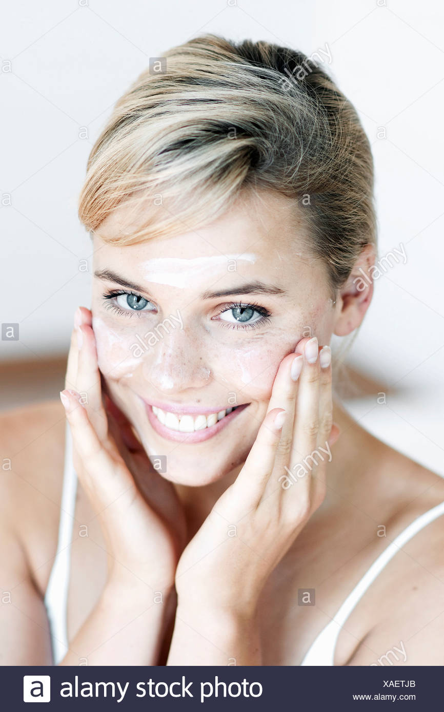 Female with fair hair tied at the back, applying face cream to her cheeks, smiling, looking at camera - Stock Image