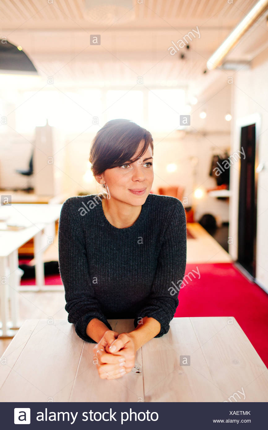 Thoughtful businesswoman with hands clasped leaning on desk in office - Stock Image