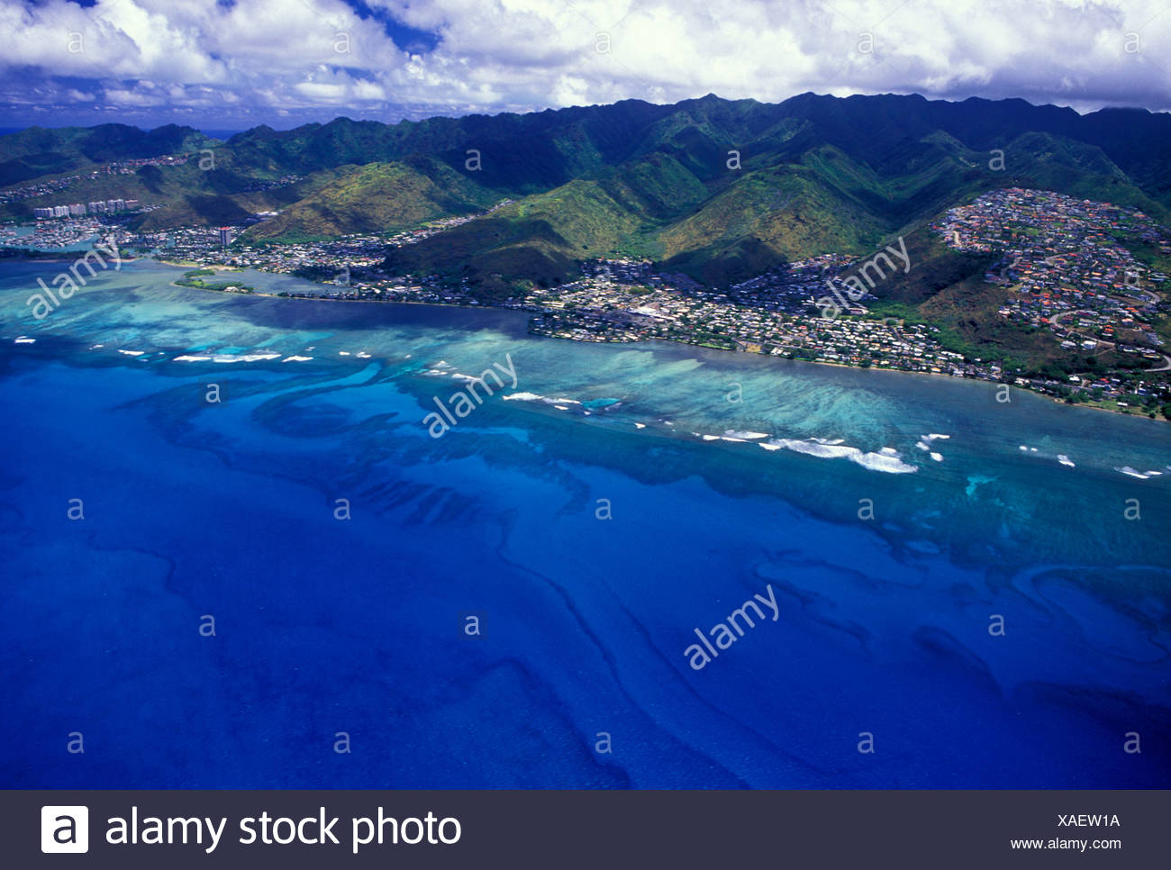 Aerial view of east Oahu with homes along the hillside mountains and wide sweeping view of the blue pacific ocean - Stock Image