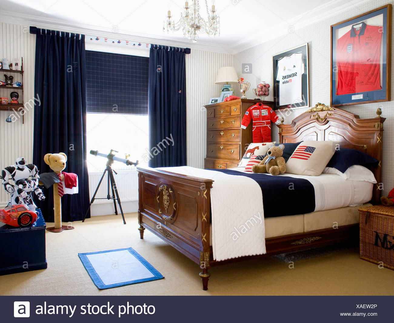 Framed Football Shirt On Wall Above Antique Mahogany Double Bed In Child S Bedroom With Black Curtains Stock Photo Alamy