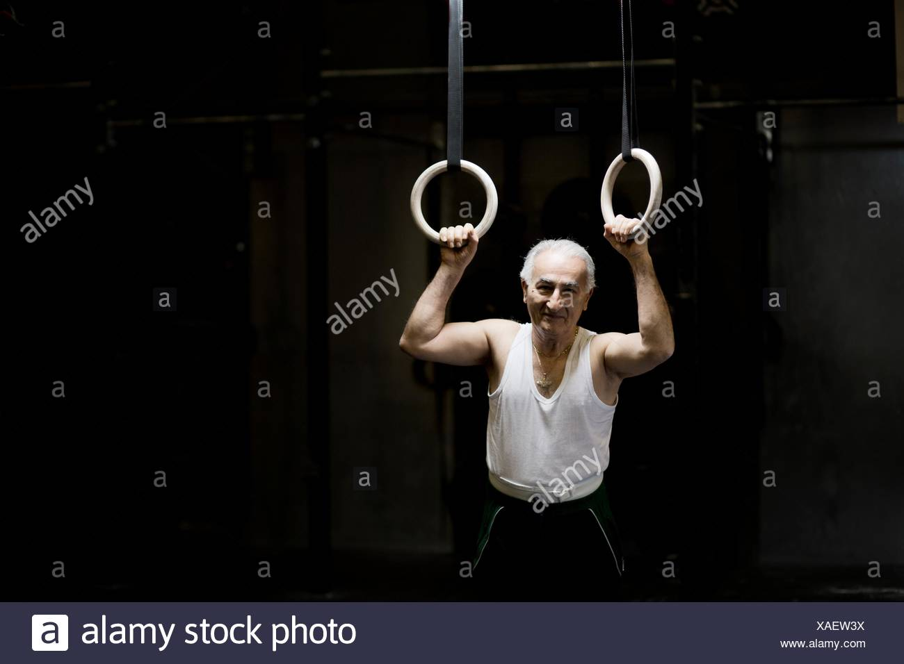 Portrait of grey haired senior man holding gym rings in dark gym - Stock Image