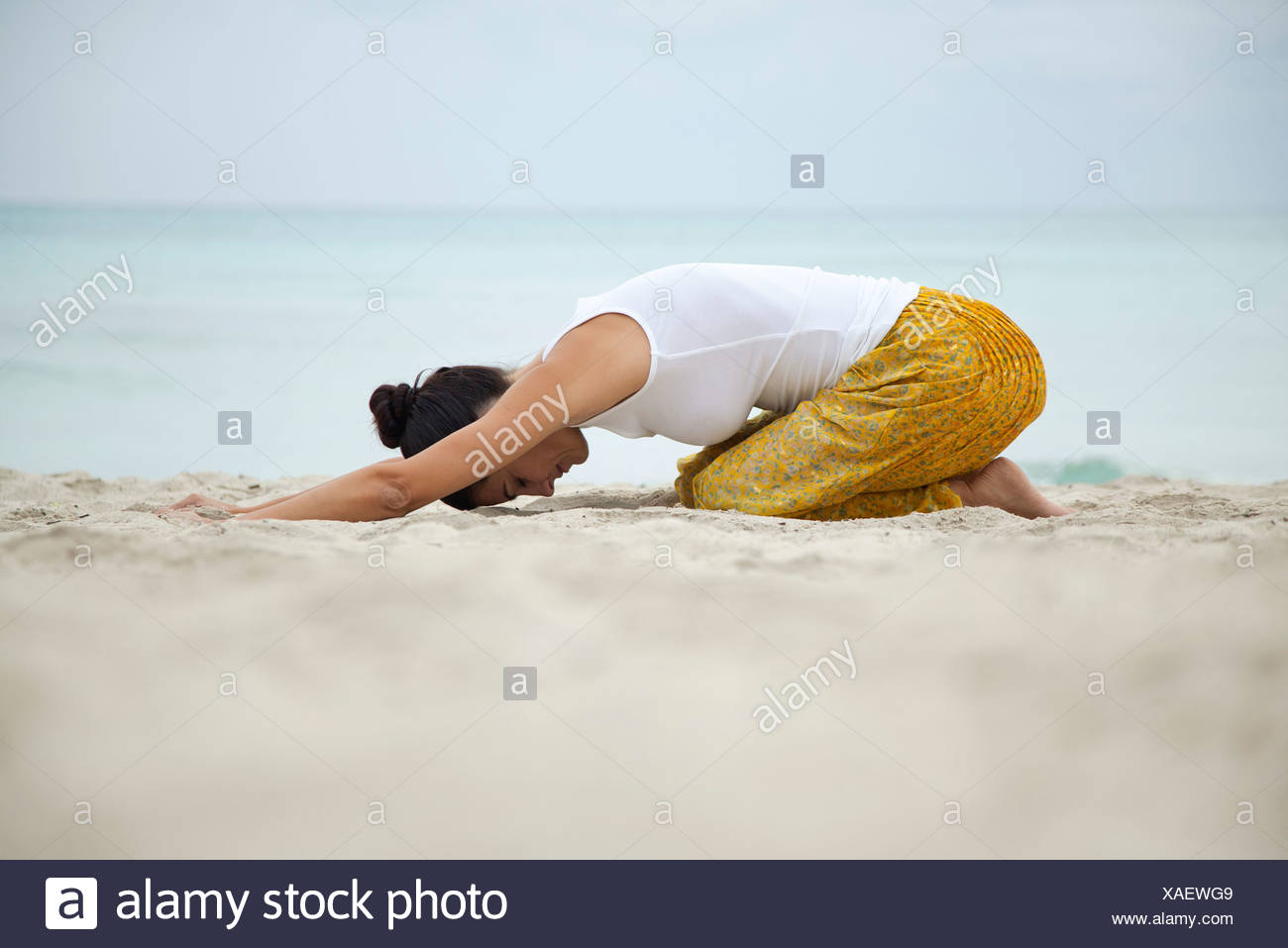 Woman in childs pose on beach, side view - Stock Image