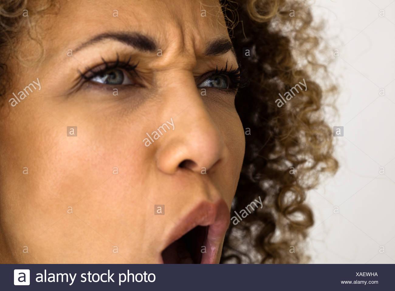 Woman furrowing brow, shouting , close-up - Stock Image