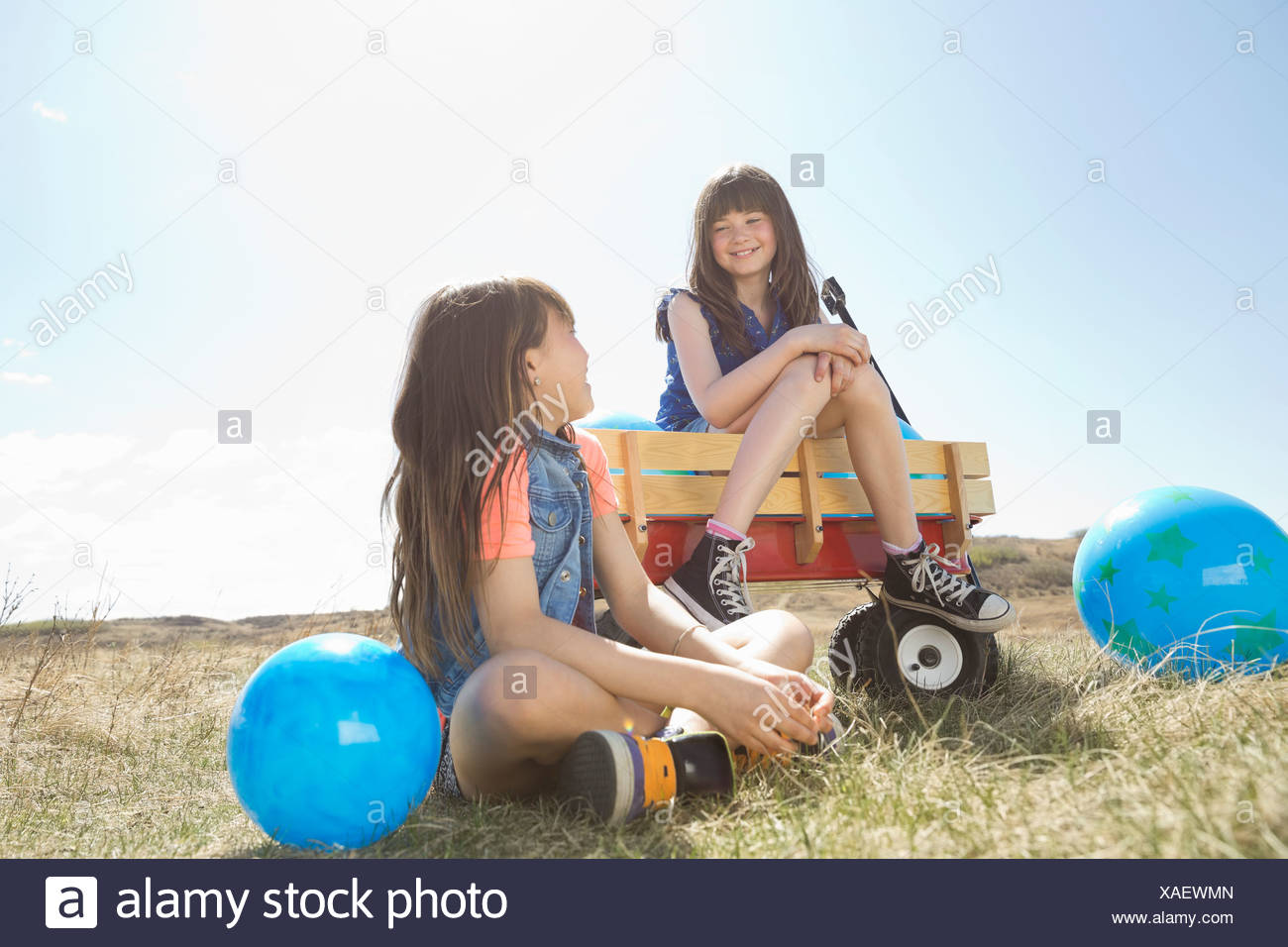 Smiling girls with balloons looking at each other - Stock Image