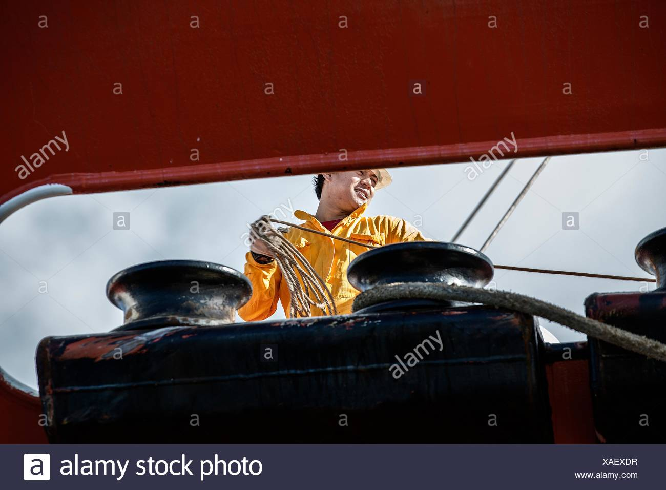 Worker fastening ropes to mooring posts on board oil tanker - Stock Image