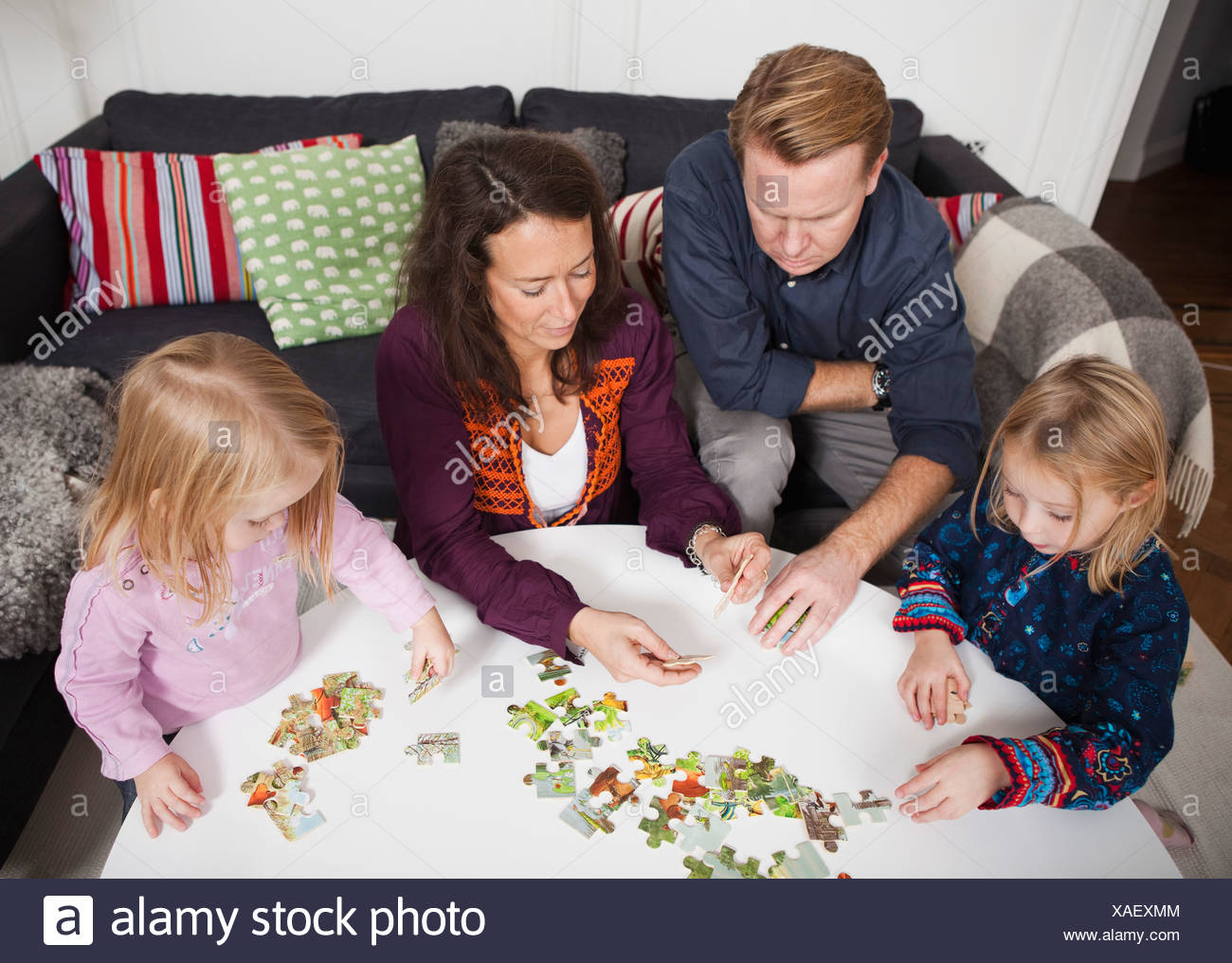 Parents and children (2-4) playing puzzle game Stock Photo