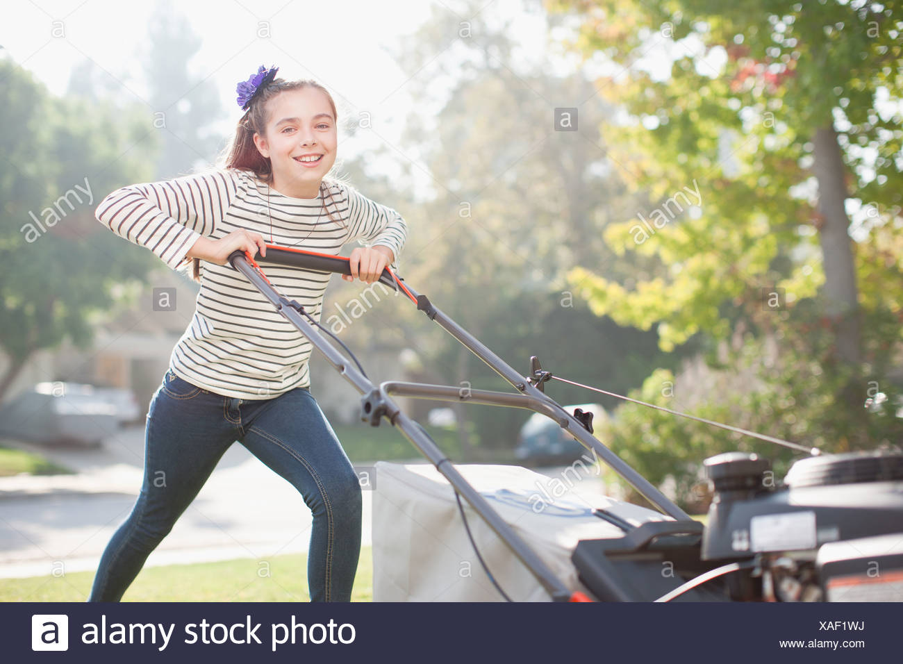 Girl mowing lawn - Stock Image