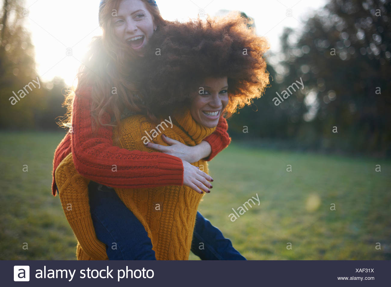 Two young women,in rural setting,young woman giving friend piggyback ride - Stock Image