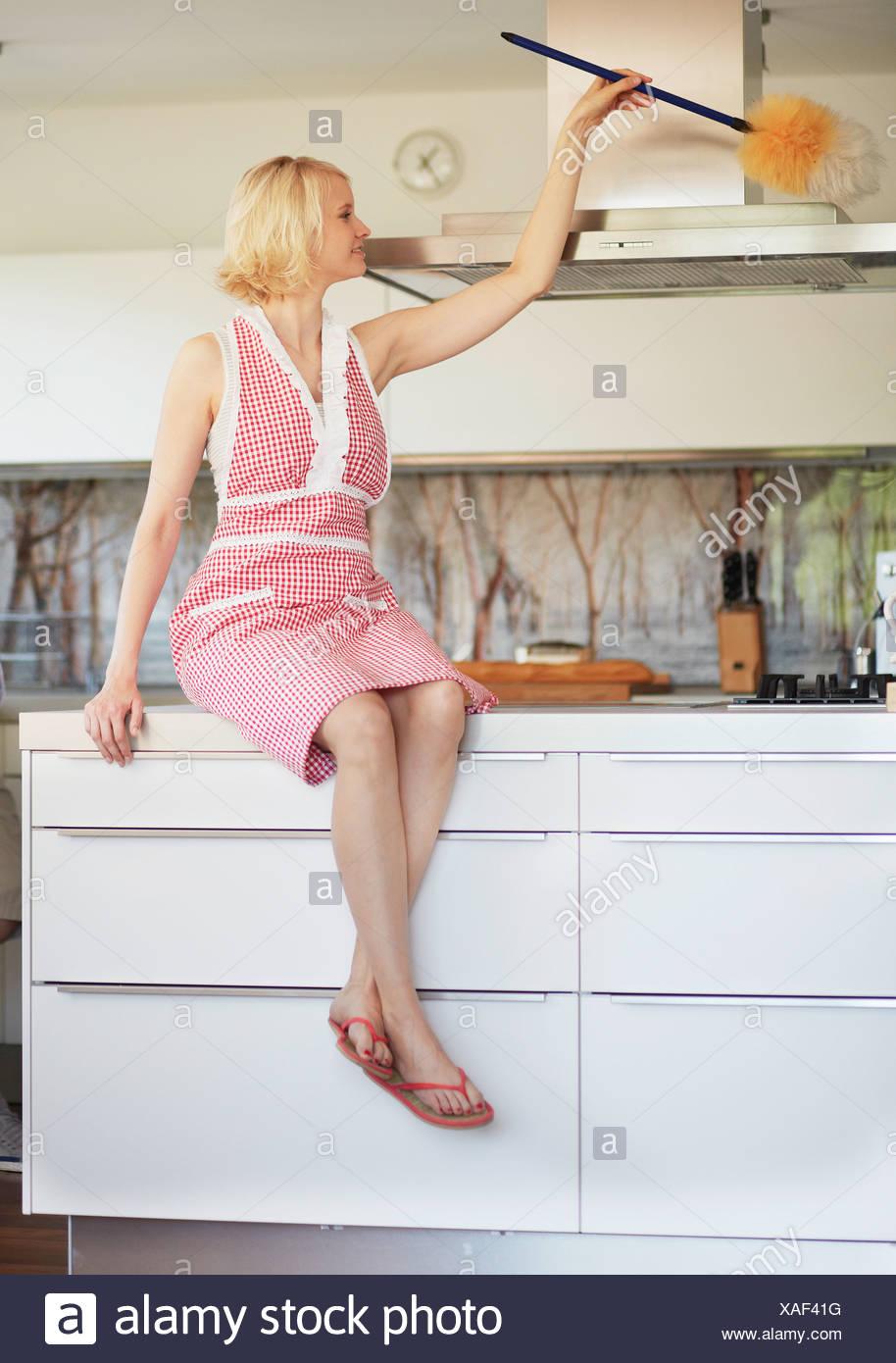 Woman dusting fan in kitchen - Stock Image