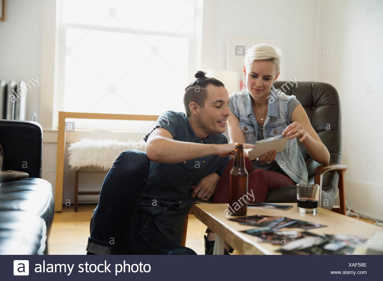 Couple looking at photographs in living room - Stock Image