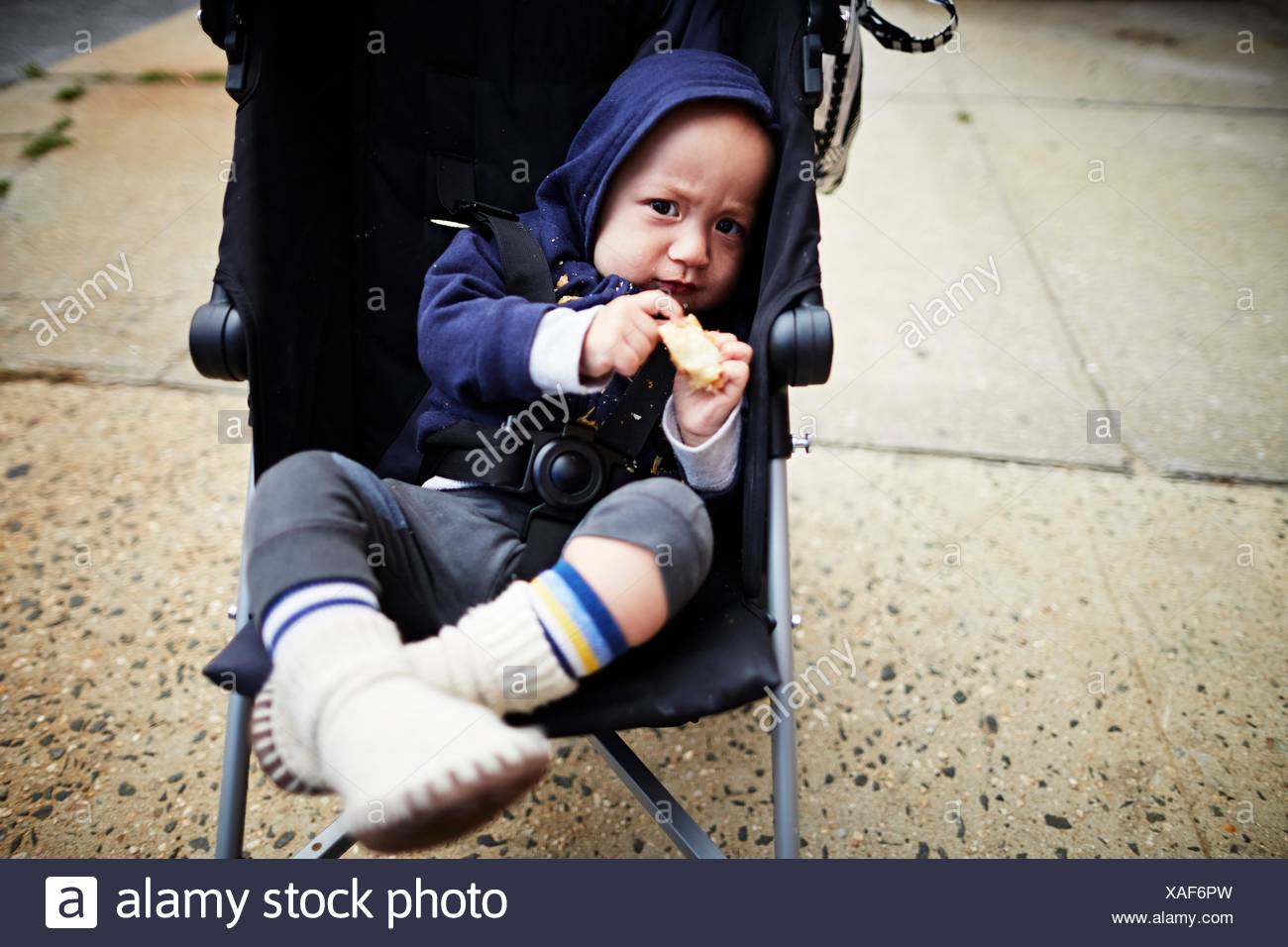 Baby boy holding cookie in carriage - Stock Image