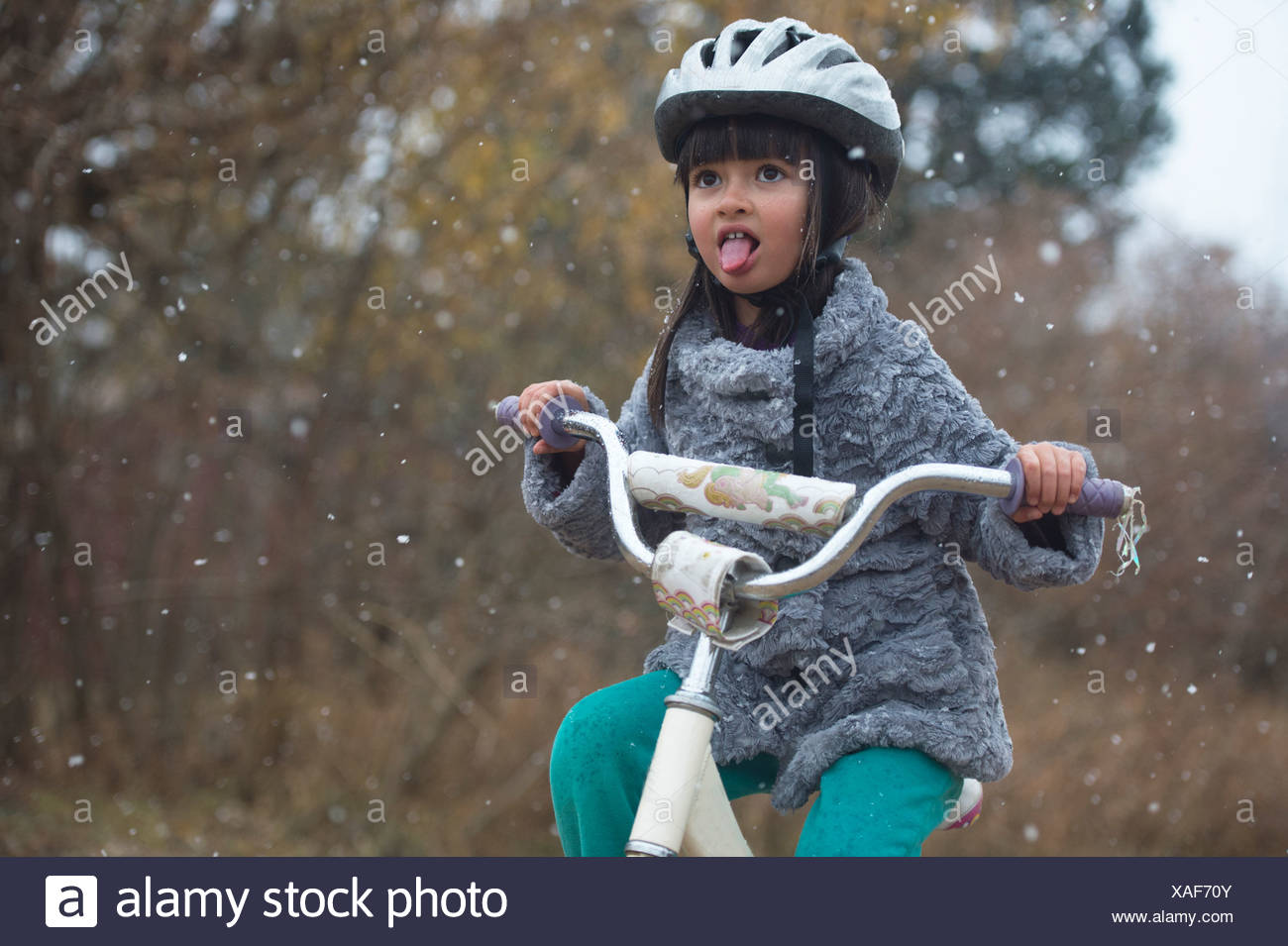 A girl rides her bike in the year's first snow fall. - Stock Image