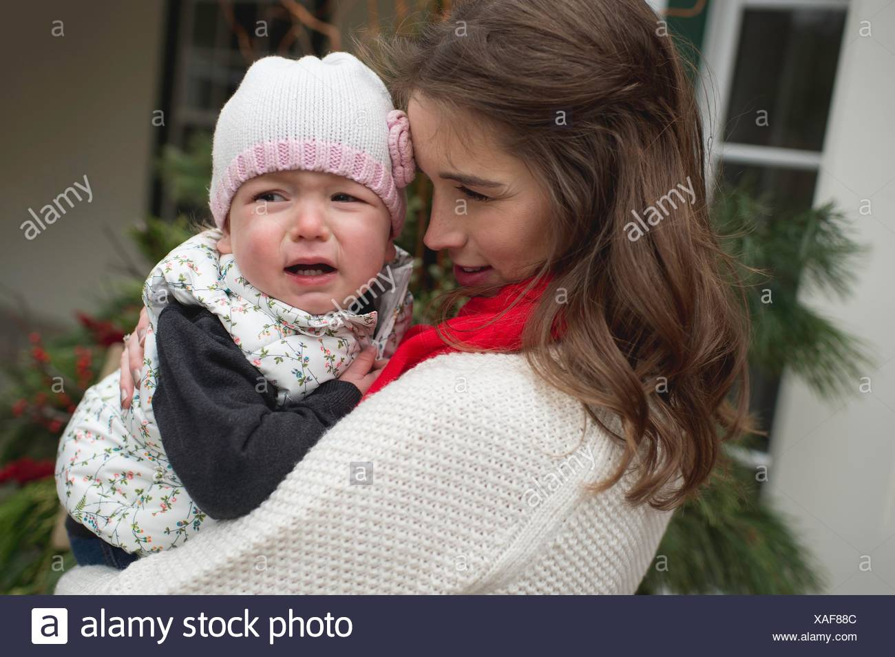 Young girl, crying, being consoled by mother, outdoors - Stock Image