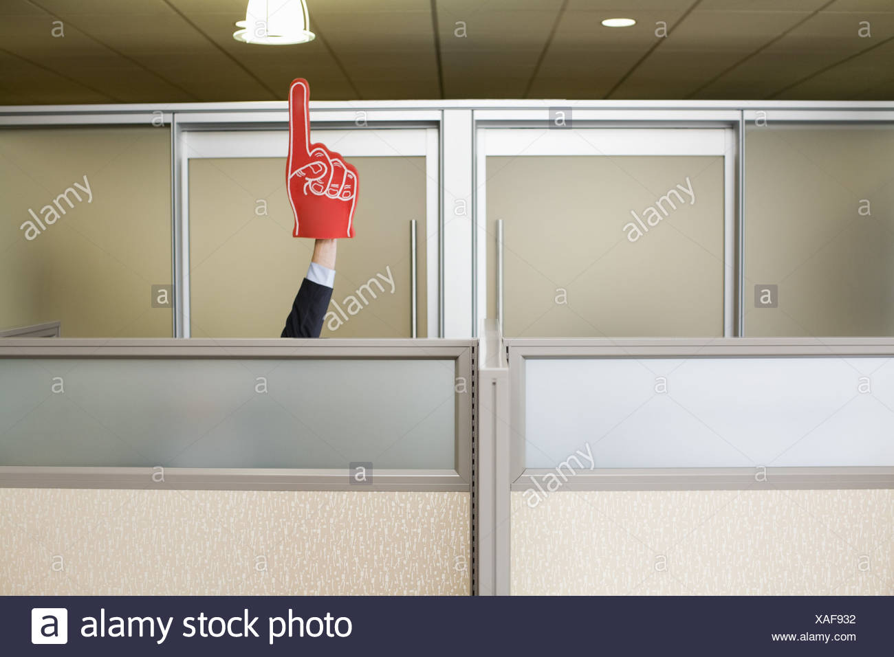 Businessman holding up sports foam finger - Stock Image