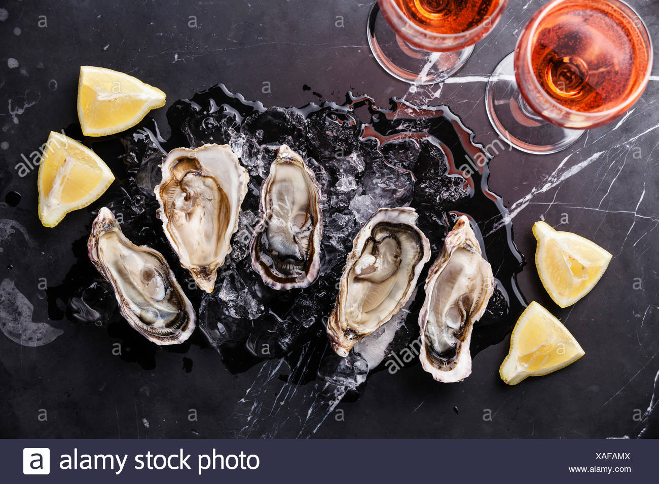 Opened Oysters on dark marble background with ice, lemon and rose wine - Stock Image